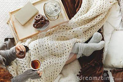 Top view of young girl covered with cozy white blanket siting on bed drinking tea and eating