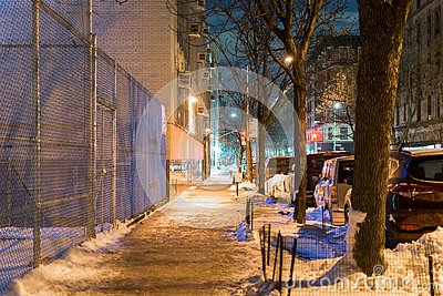 Calm and serene night scene showing an empty and quiet street in New York City`s Harlem neighborhood