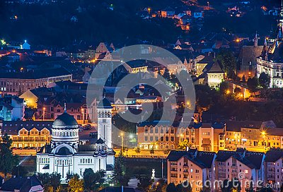 Top panoramic view of illuminated orthodox church and old buildings in downtown of Sighisoara, Romania at night