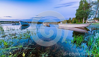 Motor and row boats anchored on the calm summer lake, sunset time, boats reflected in the water. Northern Sweden