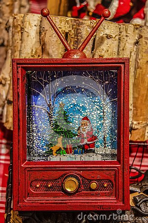 Retro Christmas Ornament - Vintage red television set with santa & snow scene behind plastic - Rustic background blurred