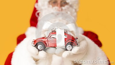 Blurred Santa Claus suggesting toy car with present bow