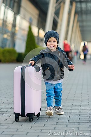 Beautiful happy girl travels with stylish suitcase. Little child traveler goes to the trip from airport.