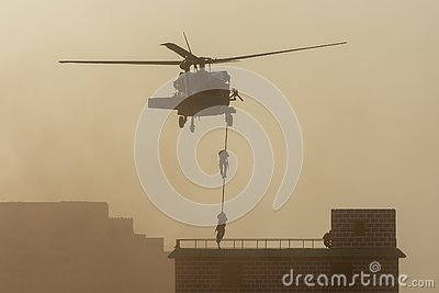 Military combat and war with helicopter flying into the chaos and destruction. Soldiers suspend from rope to the ground from
