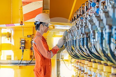 Electrical and instrument technician calibrating actuated choke valve positioner transmitter at offshore oil and gas platform.