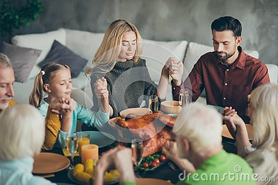 Large family gathering on thanksgiving day sit table enjoy october meal hold hands pray meeting mature relatives small