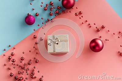 Silver small gift on pink and blue pastel backgrounds with red Christmas balls and beads. The concept of giving gifts, surprises,