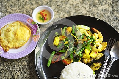 Fried stir spicy sea food with steamed rice and fried egg
