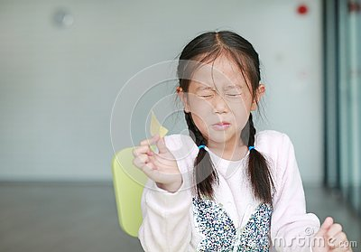 Portraits of cute Asian little girl eating crispy potato chips with face emotion feeling sour