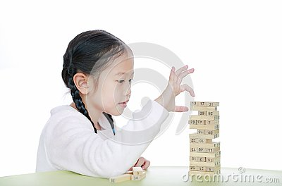 Intend little Asian child girl thinking to playing wood blocks tower game for Brain and Physical development skill in a classroom