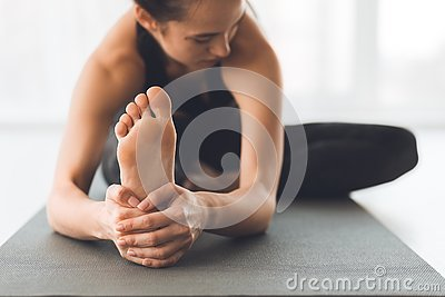 Fit woman warmup stretching, training indoors, focus on foot