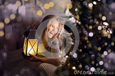 Portrait of a cheerful cute girl near a Christmas tree with a lantern. New Year holidays