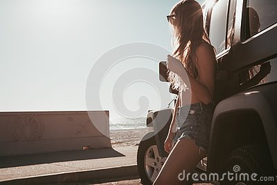 Surfer girl standing by a car at the beach. california lifestyle