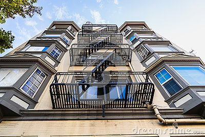 Exterior view of multifamily residential building; Old metal fire escape stairs hanging on side of the building; Berkeley, San