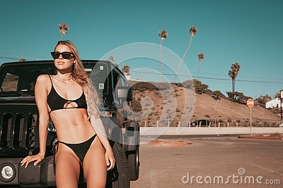 Surfer girl standing by a car on parking spot. california lifestyle