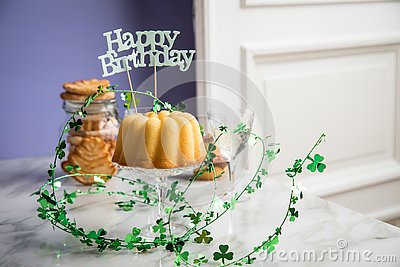 Happy birthday ring cake, cookies, biscuits, muffins and champagne  with clover decoration on marble table and lilac background