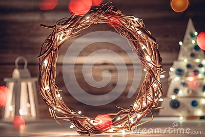 Cozy rustic composition with wreath, Christmas tree and lantern on old wooden boards background