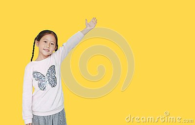 Little child girl standing and points hand up present something isolated on yellow background with copy space. Asian schoolgirl in