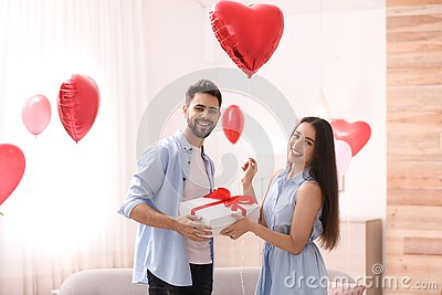 Young man presenting gift to his girlfriend in room decorated with heart shaped balloons. Valentine`s day celebration