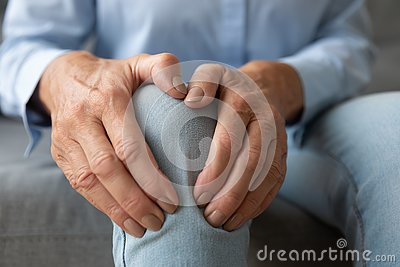 Old woman touching knee feeling pain suffering from osteoarthritis, closeup