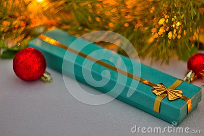Christmas gift in a blue box with gold ribbon lies under the Christmas tree. red Christmas balls and a beautiful spruce