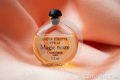 Magie noire de Lancome, traduction in english : black magic in miniature bottle of perfume on satin background