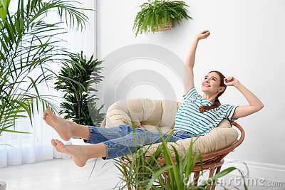 Young woman in room decorated with plants