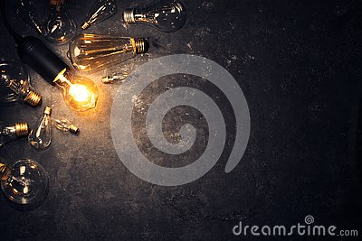 Vintage old light bulb glowing on rough dark background surrounded by burnt out bulbs. Idea, creativity concept