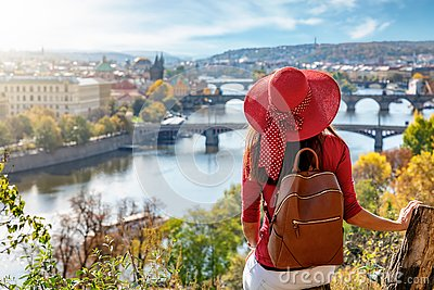 A traveler woman with red hat enjoys the elevated view over the city of Prague, Czech Republic