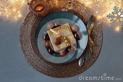 Top view on Christmas table setting. Golden decoration with gift box, glass baubles and defocused lights. Christmas and New Year