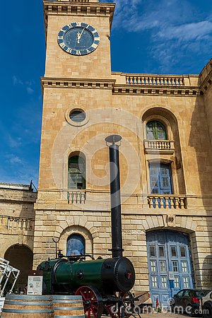 Clock tower of Malta Maritime Museum with old steam engine in front