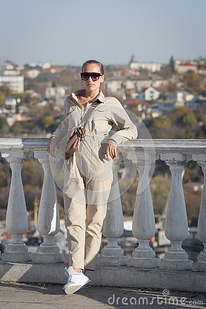 Attractive young woman in tinted sunglasses and overalls posing leaning on balustrade crossed legs and looking at camera