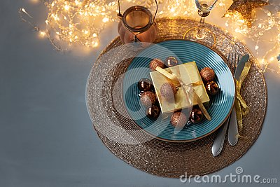Christmas table setting. Golden decoration with gift box, glass baubles and defocused lights. Christmas and New Year holidays