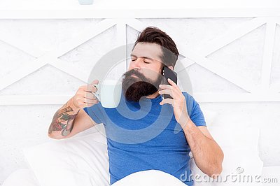Pleasant conversation. Good morning. Hello dear. Bearded man using mobile technology in bed. Handsome guy talking on