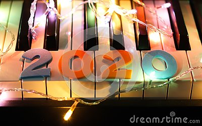 Number 2020 on piano keyboard with glowing string light