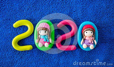 Happy New Year 2020 , molding of color clay with little girls toys on blue background.