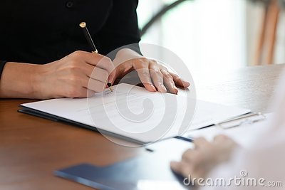 Close up cropped image young woman signing business agreement.