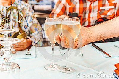 The waiter serves two glasses of white wine for a couple.  Man and woman have a lunch on a restaurant