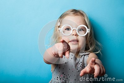 A little girl points with fingers and hands. Toy fashion glasses