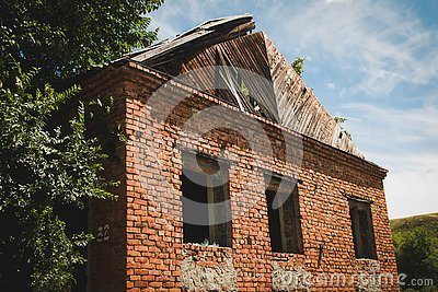 Old ruined red brick building with empty windows