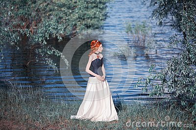 Young renaissance princess with red necklace and hairstyle on nature background. Rococo queen in white historic dress against