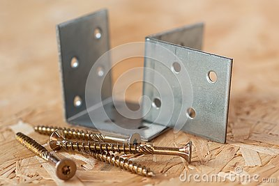 Two galvanized angle brackets and self drilling screws lying on chip board. Blurred background