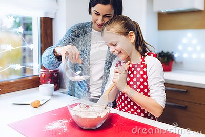 Christmas bakery. Mother and daughter making gingerbread, preparing eggs, flour and honey for gingerbread dough.