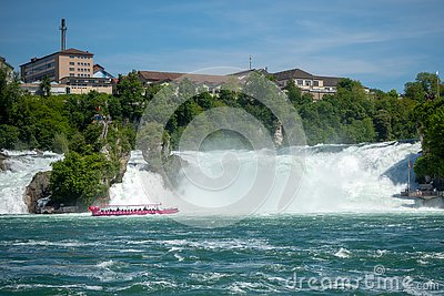 Pink boat float at rock observation on flowing river under the Rhein fall for background