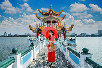 Asian woman in chinese dress traditional walking at Kaohsiung`s famous tourist attractions in Taiwan.