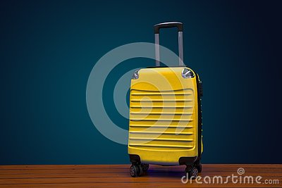 Yellow color traveling suitcase on dark background with copy space