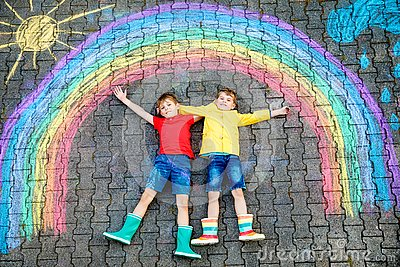 Two school kids boys having fun with with rainbow picture drawing with colorful chalks on asphalt. Siblings, twins and