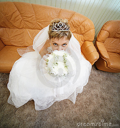 Bride sits on leathern sofa