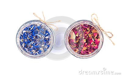 Dried blue cornflower centaurea petals and red rose petals in a glass jars isolated on white background.