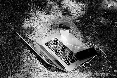 Laptop with headset of mobile phone and coffee to go on green grass. agile business. Online study. summer vibes. Relax